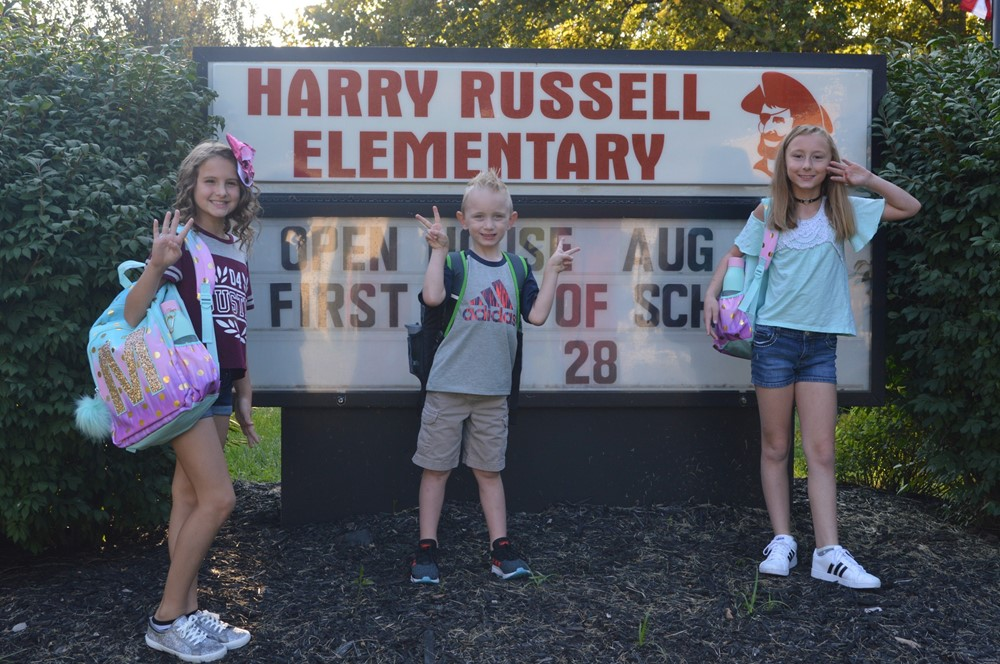 Students Pose at Russell Sign